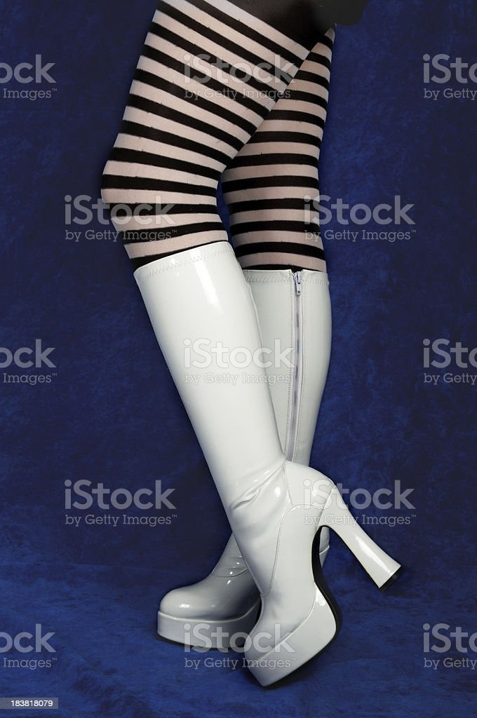 Legs in striped stockings and white boots. stock photo