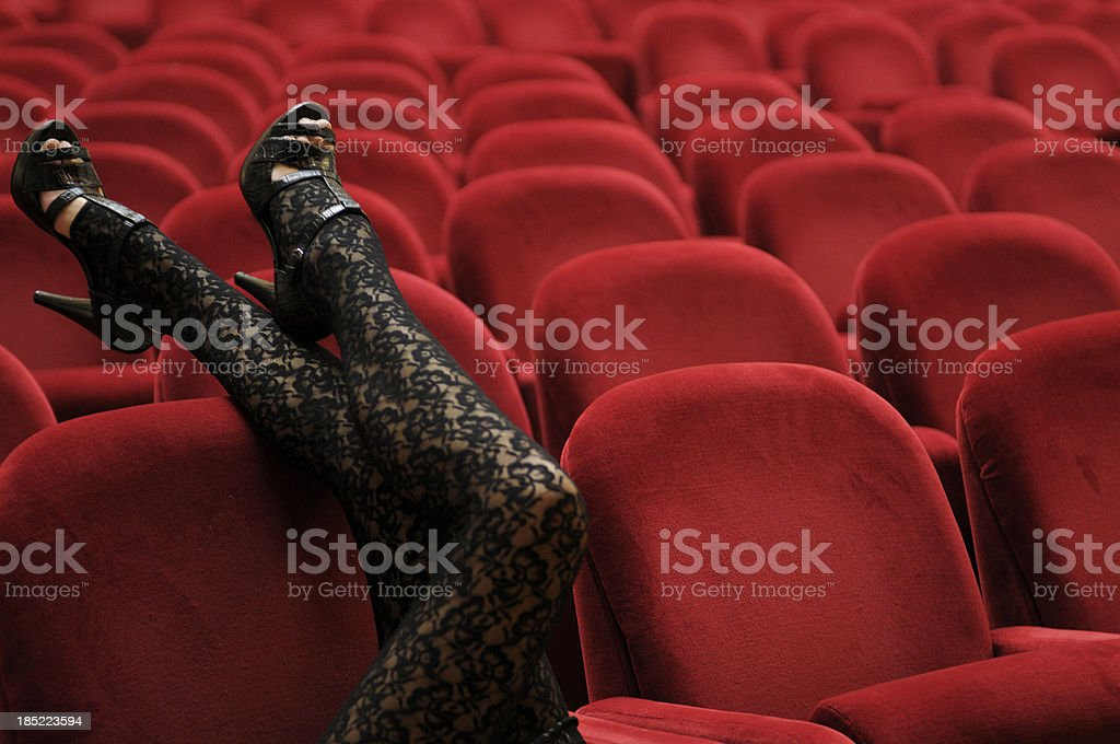 Legs Leaning on Theater Chair stock photo