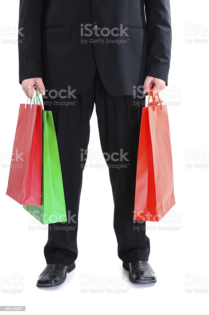 Legs of a businessman holding shopping bags royalty-free stock photo