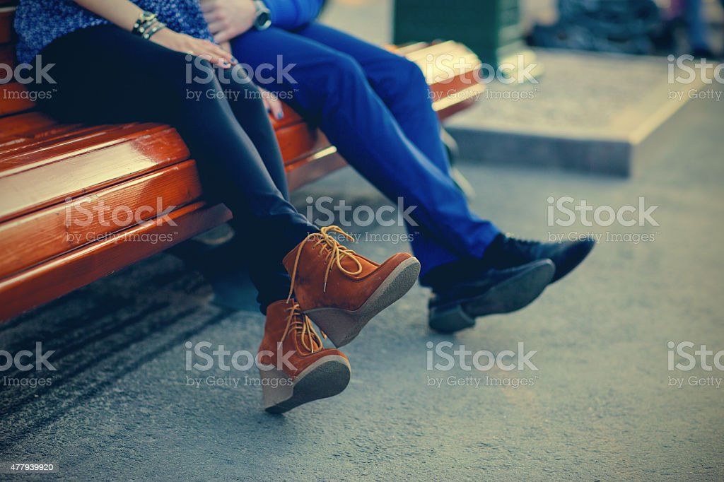 Legs of a couple sitting on a bench stock photo