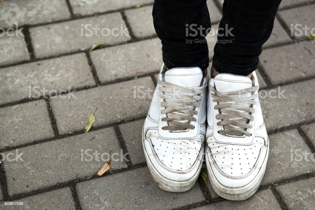 Legs of a standing teenager in sneakers stock photo