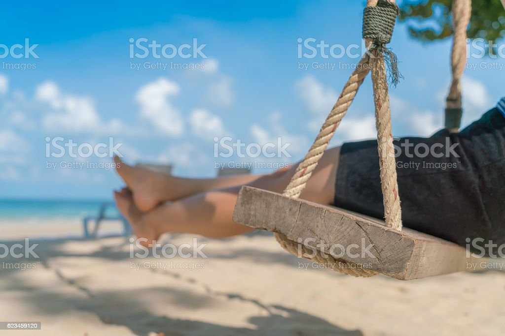 Legs of a woman on a swing stock photo