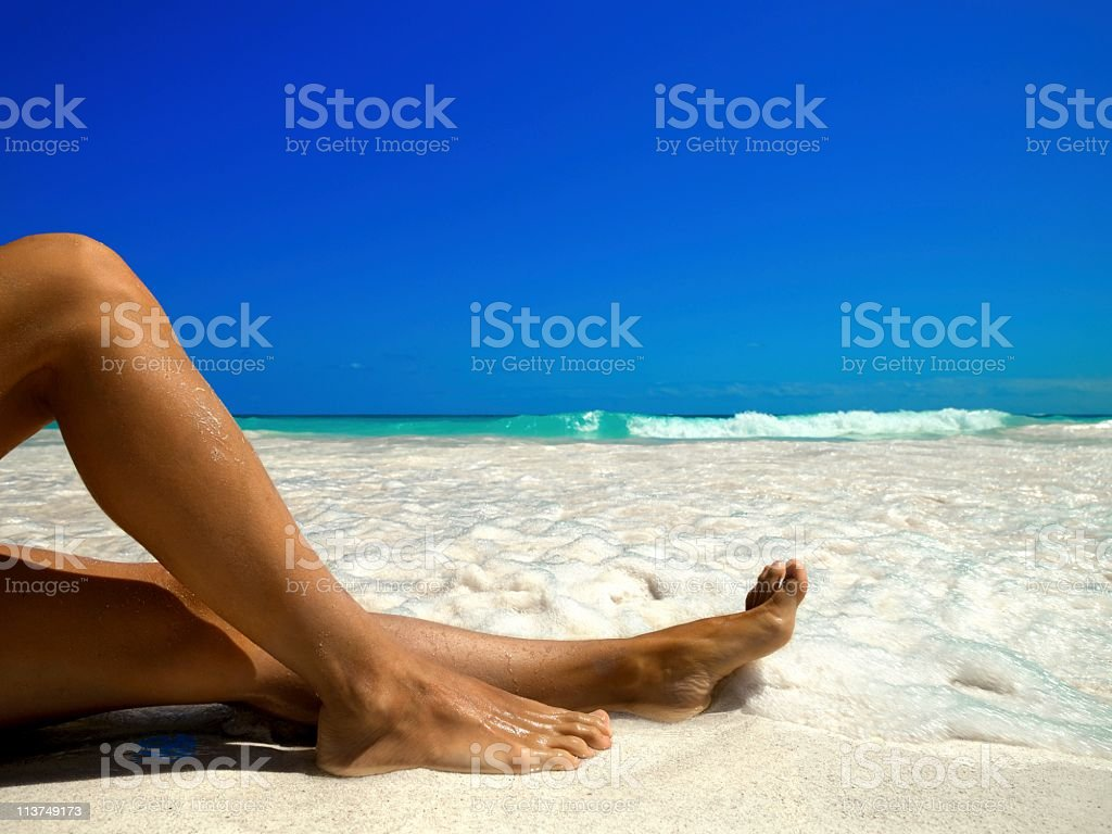 legs of a woman on the beach stock photo