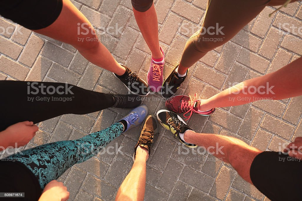 Legs of athletes in a circle stock photo