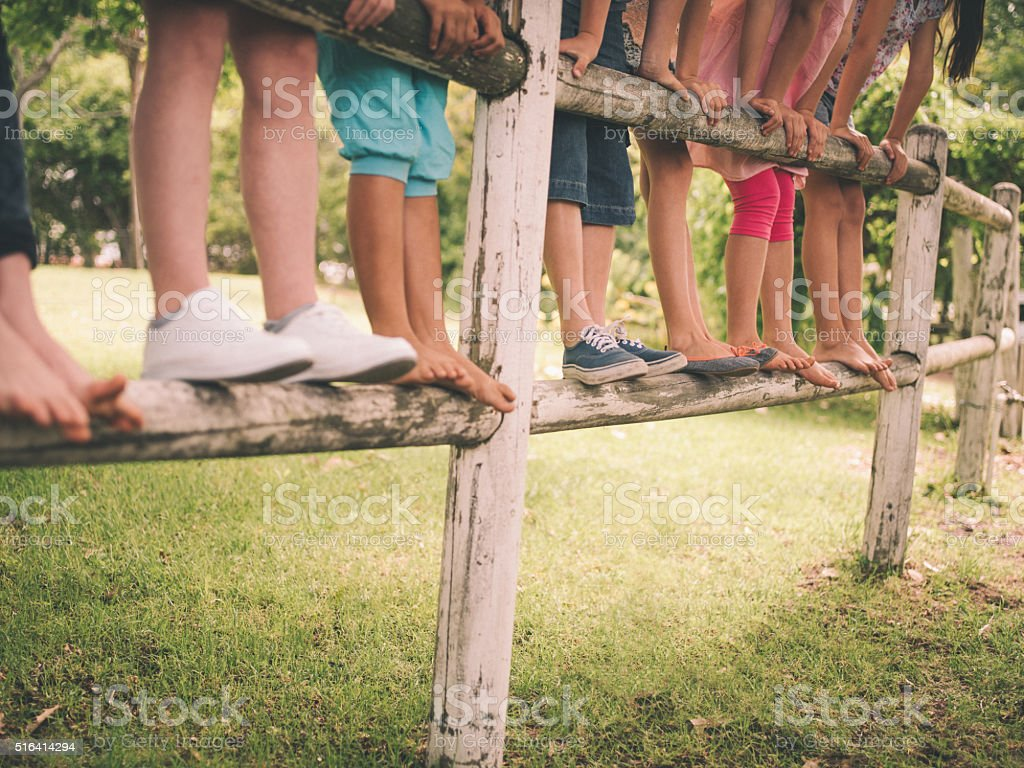 Legs of children standing on a wooden fence in park stock photo