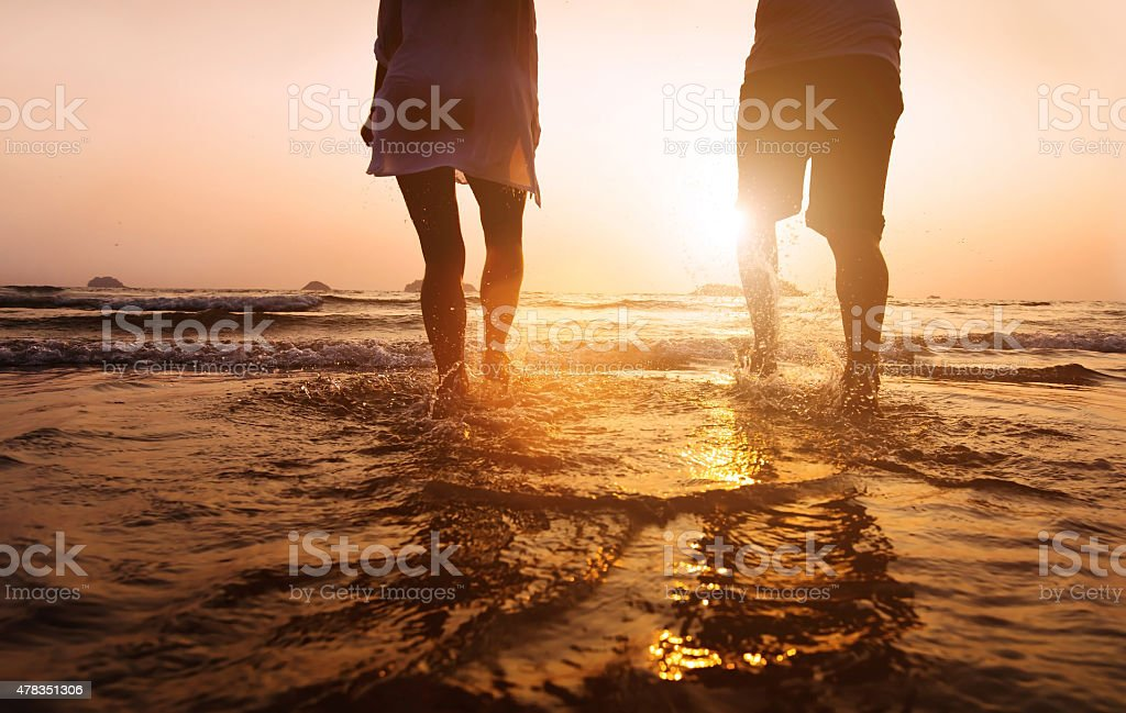legs of couple running to the sea stock photo