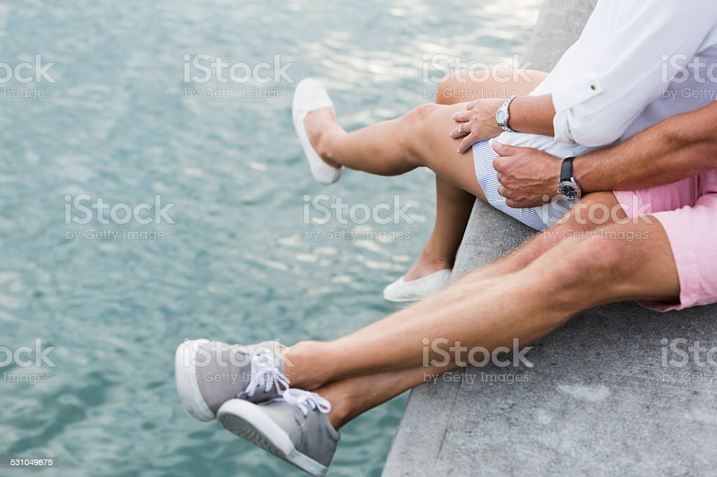 Legs of couple sitting on dock by water stock photo