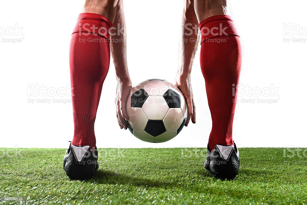 legs of football player holding ball placing free kick stock photo