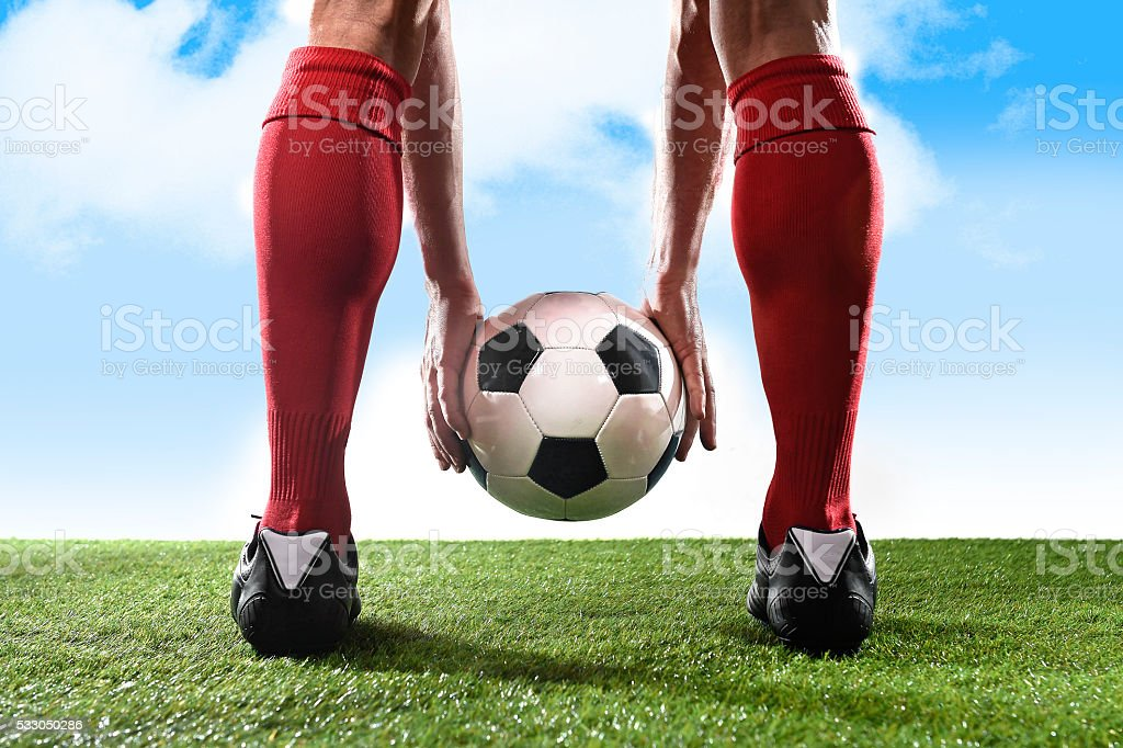 legs of football player holding ball placing free kick stock photo