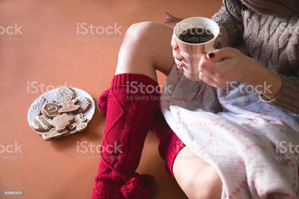 legs of girl warm socks and cup of coffee stock photo