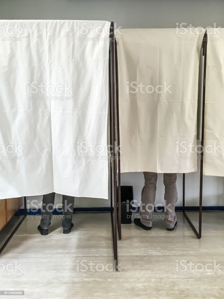 Legs of people voting in polling booths at a voting station stock photo