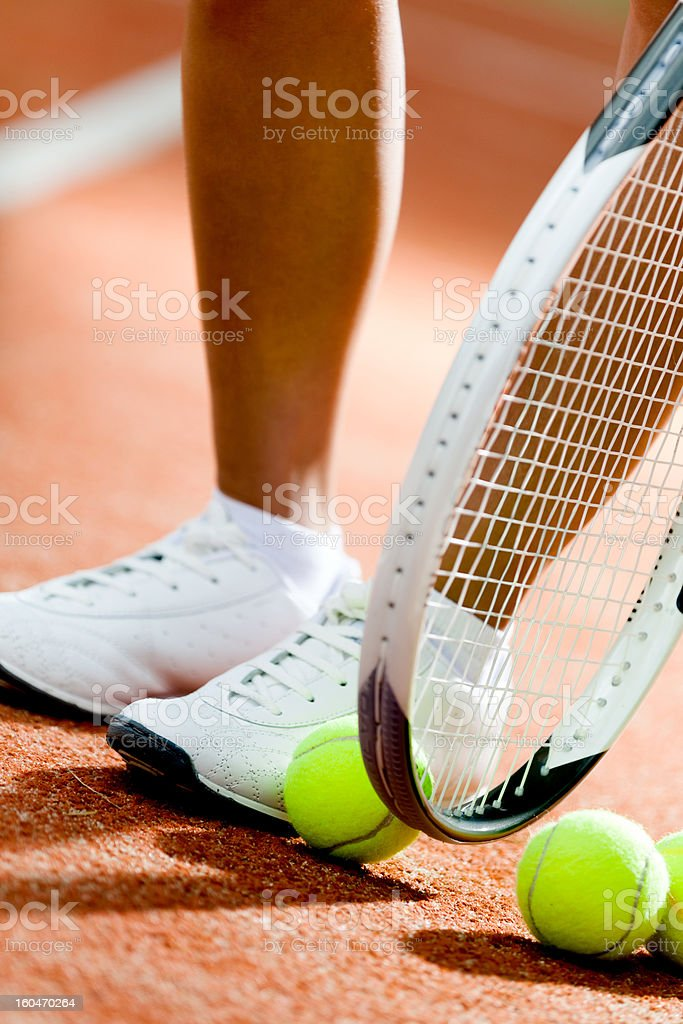Legs of sportive girl near the tennis racket and balls royalty-free stock photo
