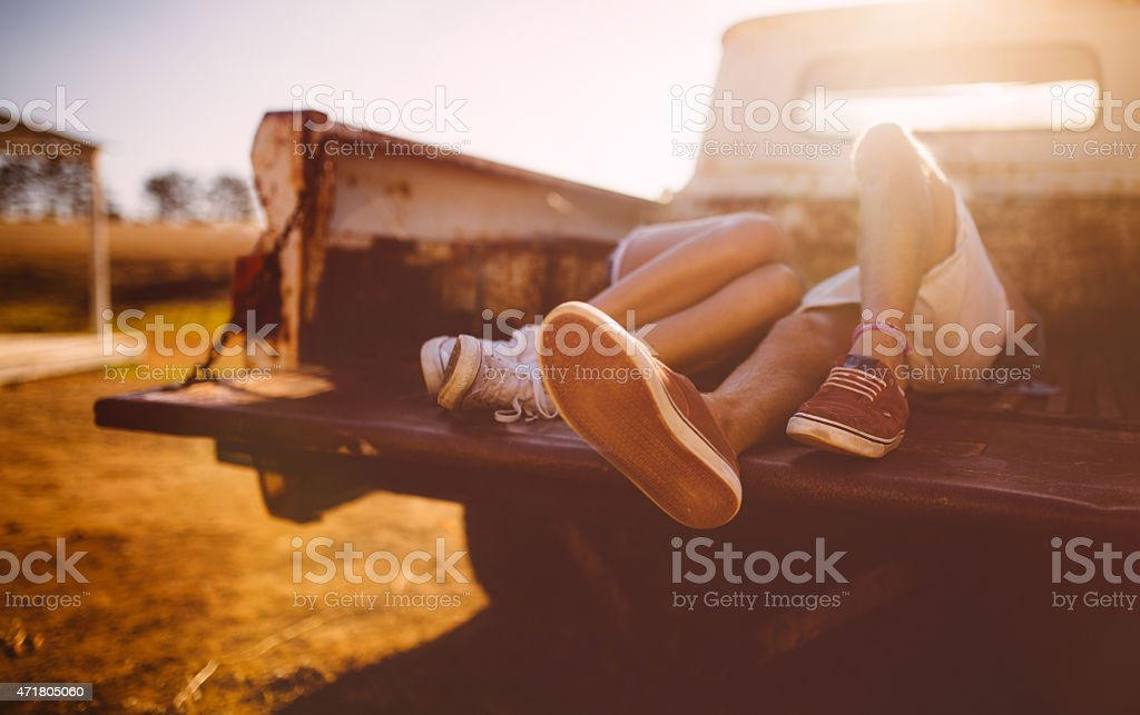 Legs of teen couple kissing in back of vintage truck stock photo