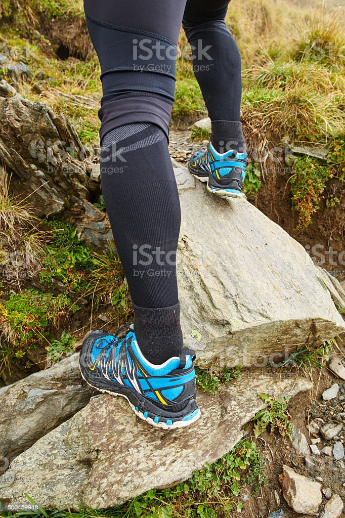Legs of trail runner climbing stock photo