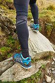 Legs of trail runner climbing