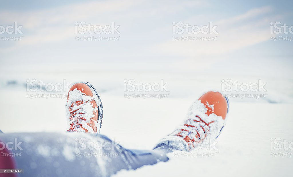 Legs of traveler sitting in snow. Travel and discovery concept stock photo