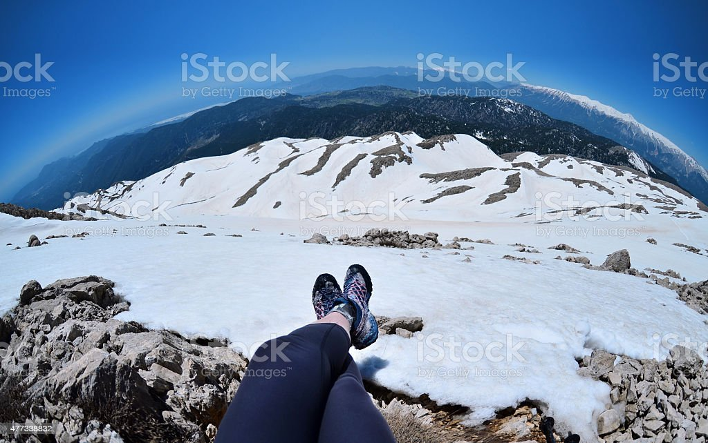Legs of traveler sitting on high mountain top in Turkey stock photo