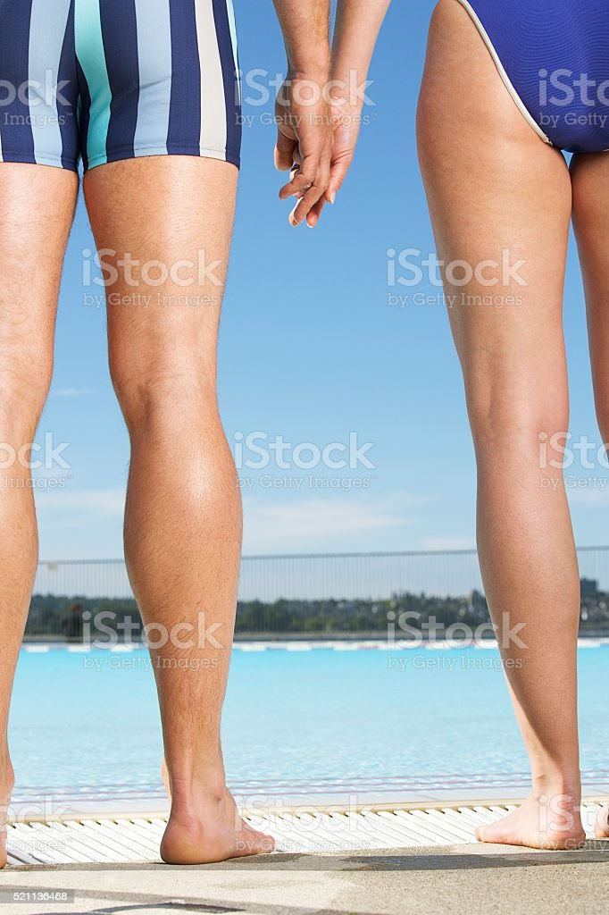 Legs of two people standing by a swimming pool stock photo