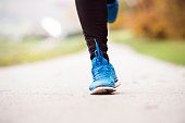 Legs of unrecognizable runner jogging on concrete path,close up
