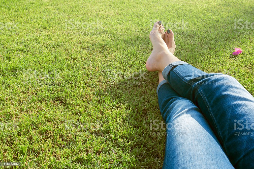 legs of woman relaxing on green grass stock photo