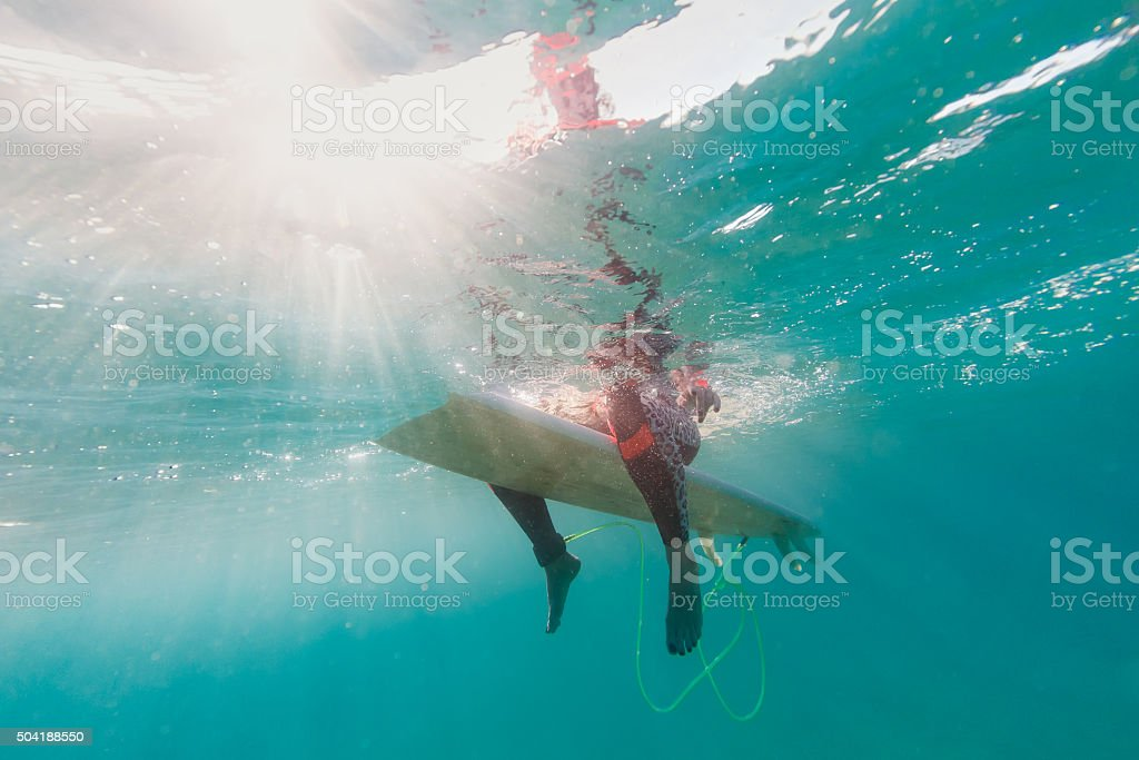 legs of woman who sitting on the surfboard underwater stock photo