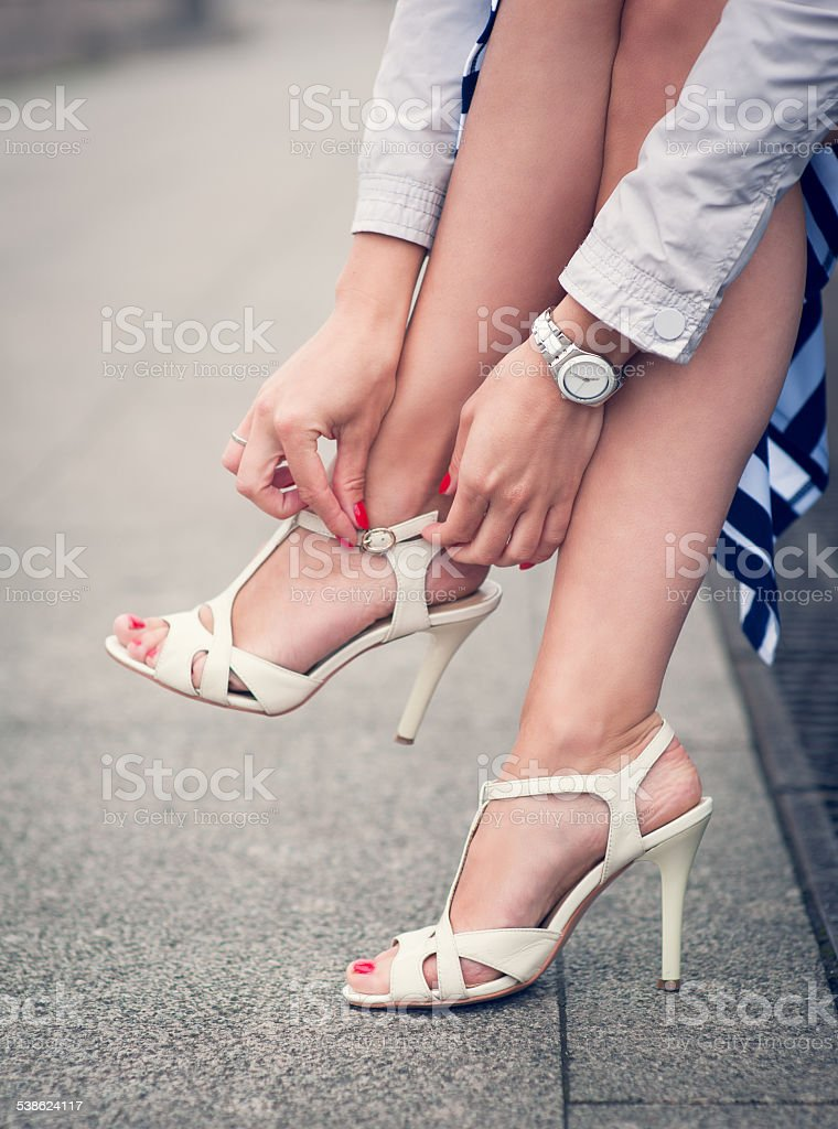 Legs of woman with high heels white sandals stock photo