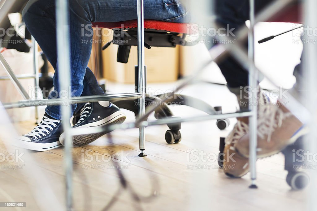 Legs Of Young Office Workers Under Table stock photo