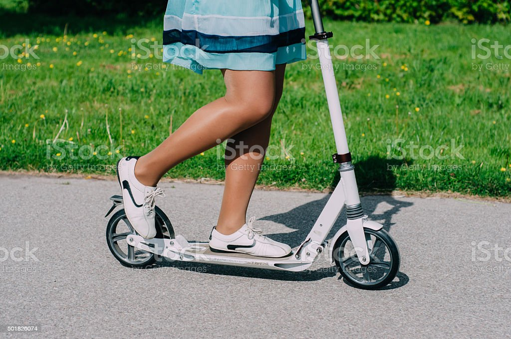 Legs of young woman on kick scooter stock photo
