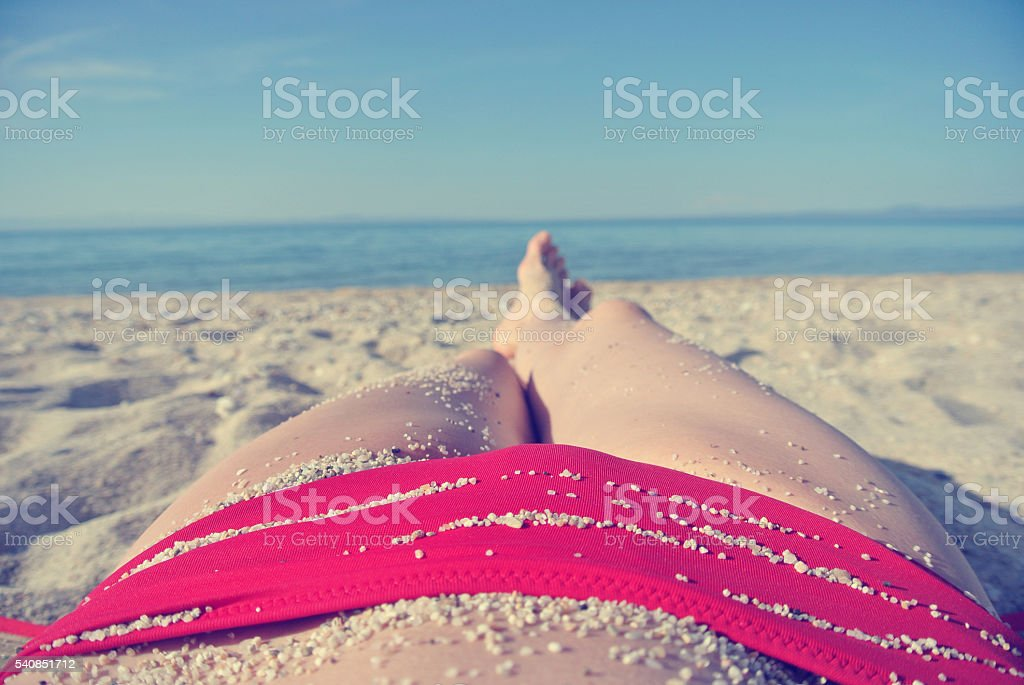 Legs of young woman on the beach; personal pov; retro stock photo