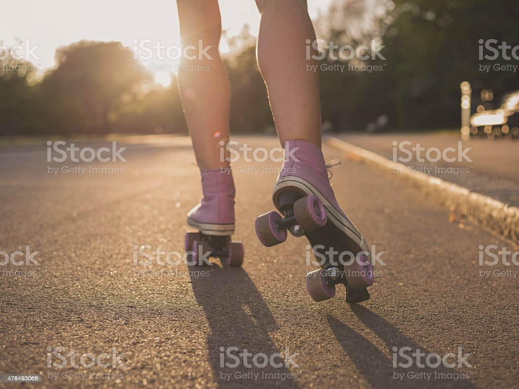 Legs of young woman roller skating in park stock photo