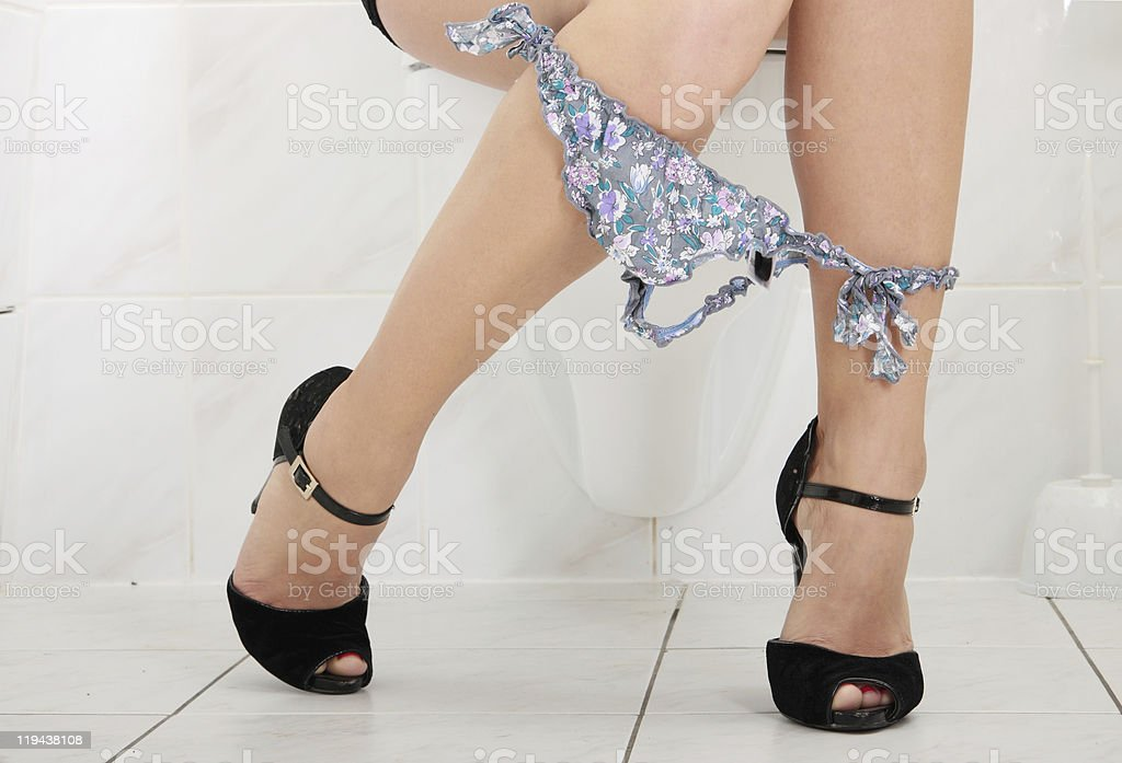 Legs of young woman sitting on toilet stock photo