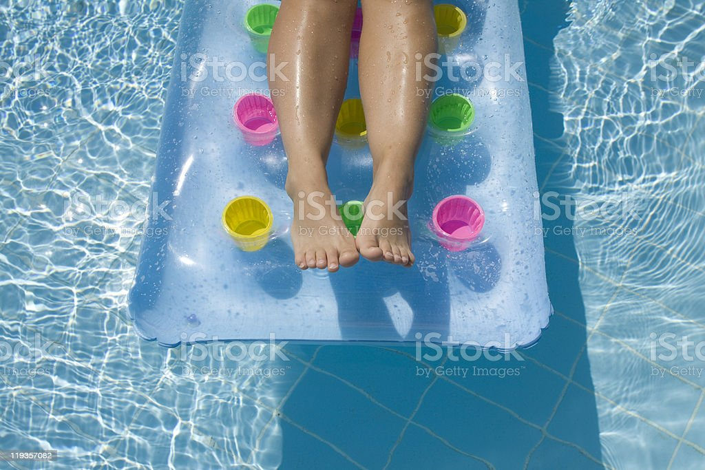 Legs on an inflatable pool mattress royalty-free stock photo