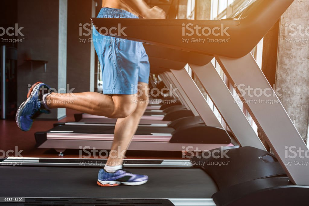 Legs running on the treadmill close up stock photo