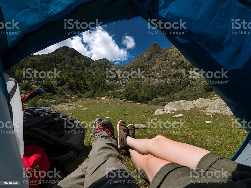 Legs sticking outside camping tent in the mountains stock photo