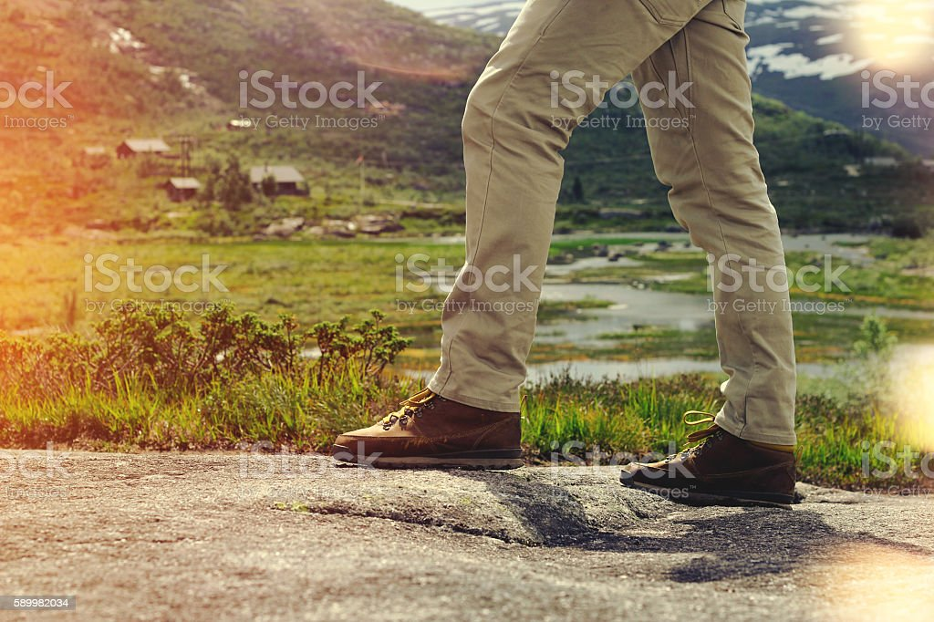 Legs traveler close-up on a background of mountain landscape stock photo
