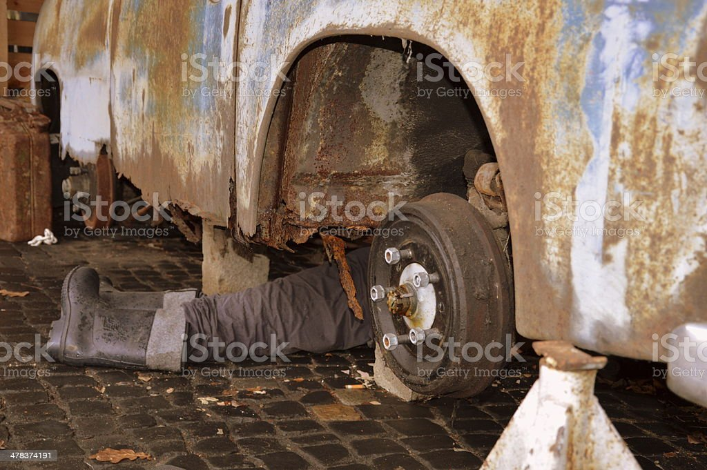 Legs under an old car royalty-free stock photo
