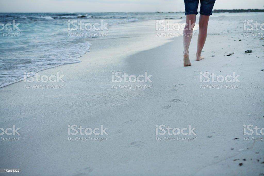 Legs walking on the beach near the sea stock photo
