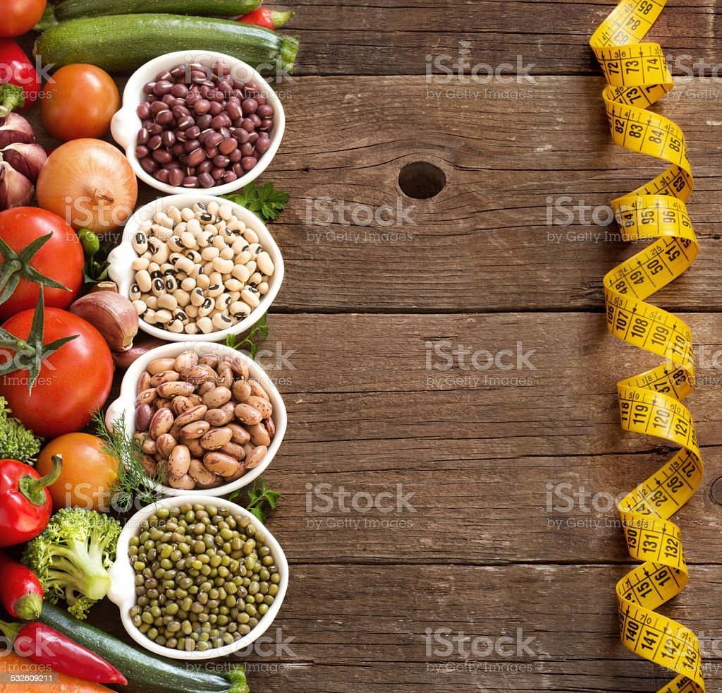 Legumes in bowls and vegetables stock photo