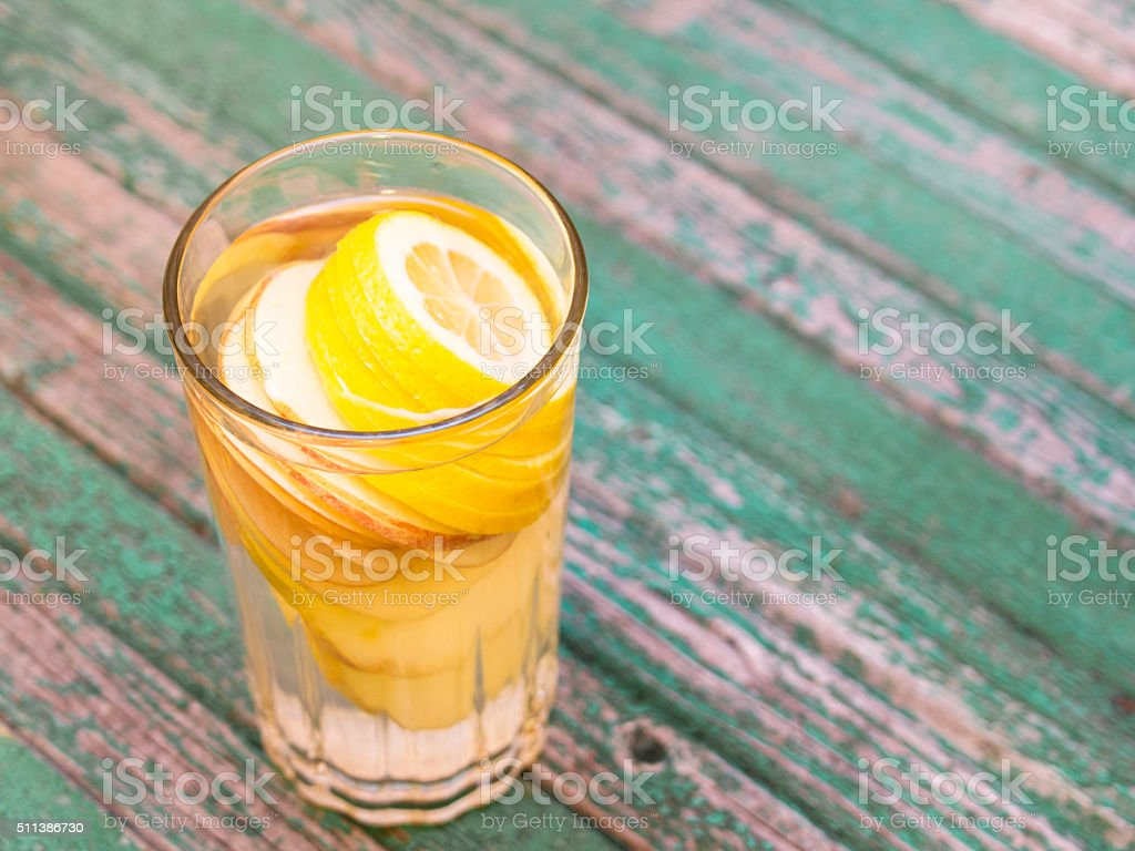 Lemon and apple Detox water in glass on a wood stock photo