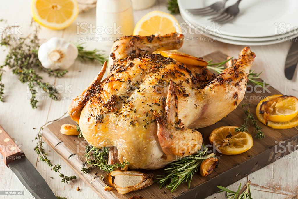 Lemon and herb whole chicken on wooden board stock photo