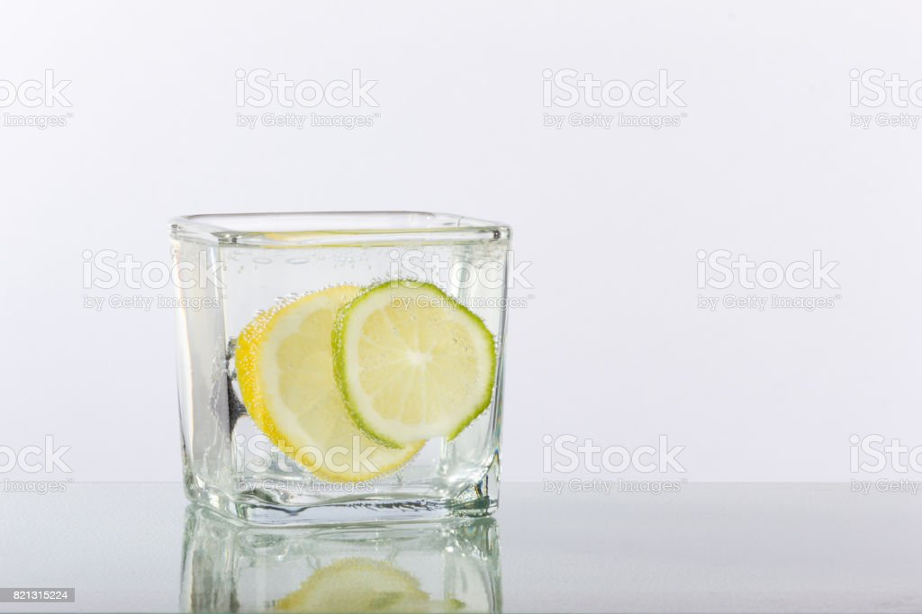 Lemon and Lime Slices in a Glass with Ice and Reflection stock photo