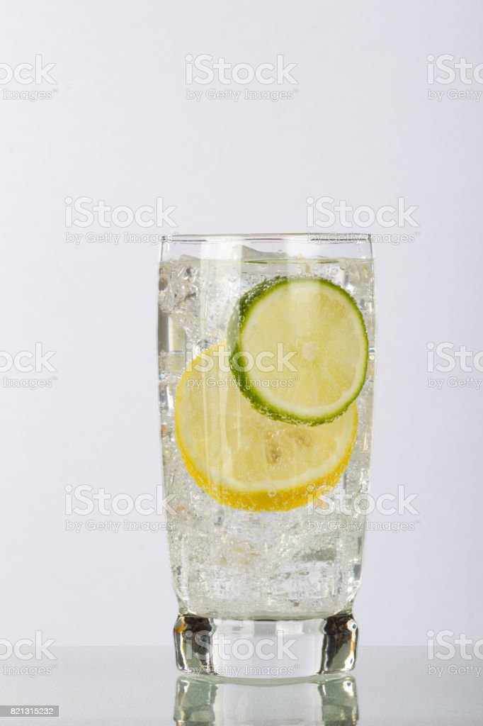 Lemon and Lime Slices with Bubbles in a Glass with Ice stock photo