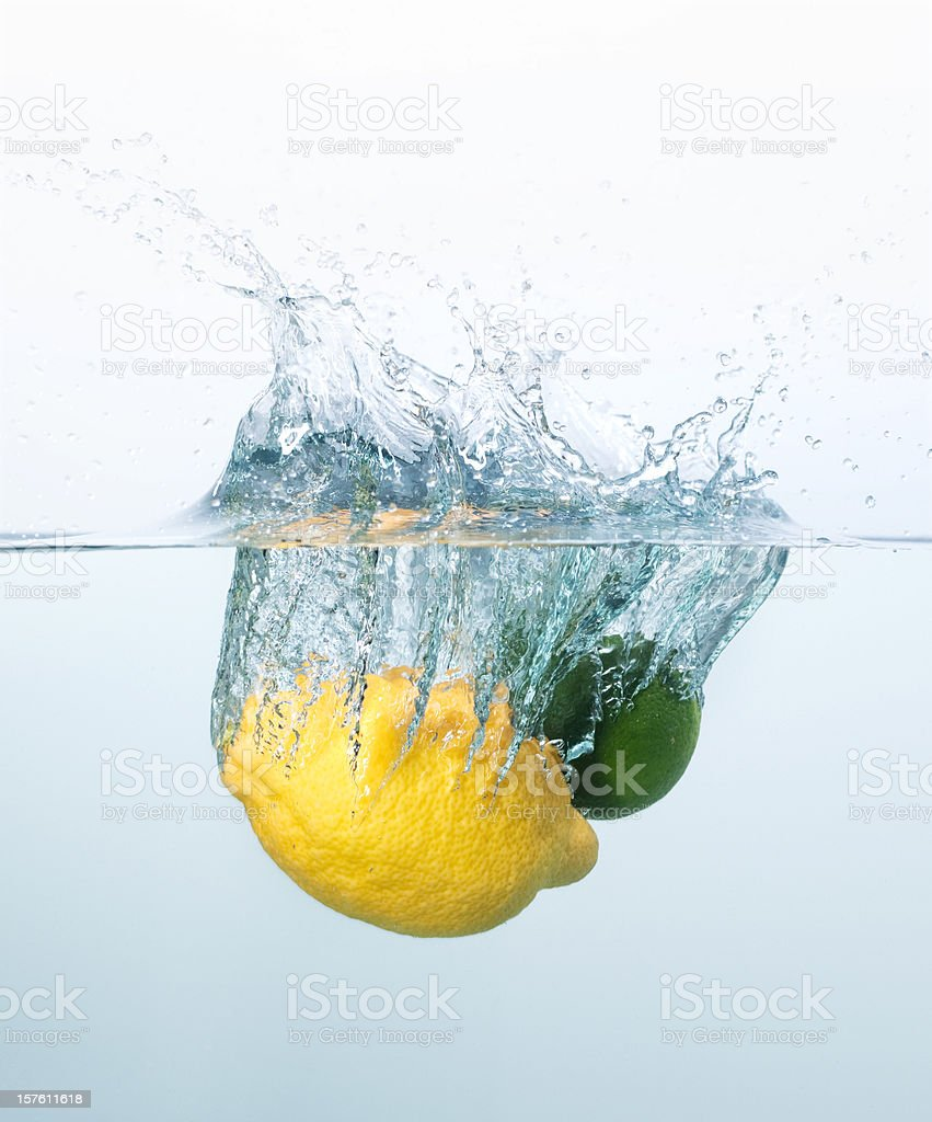 Lemon and lime splashing into the water royalty-free stock photo