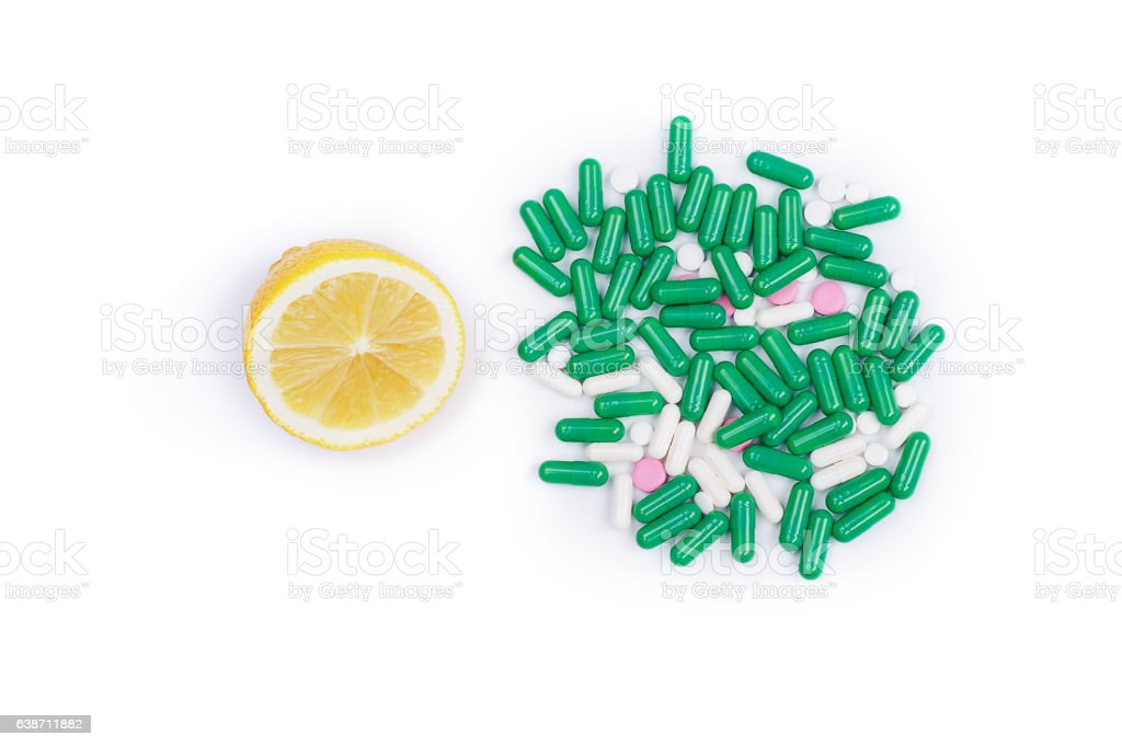 Lemon and pile of pills on white background stock photo