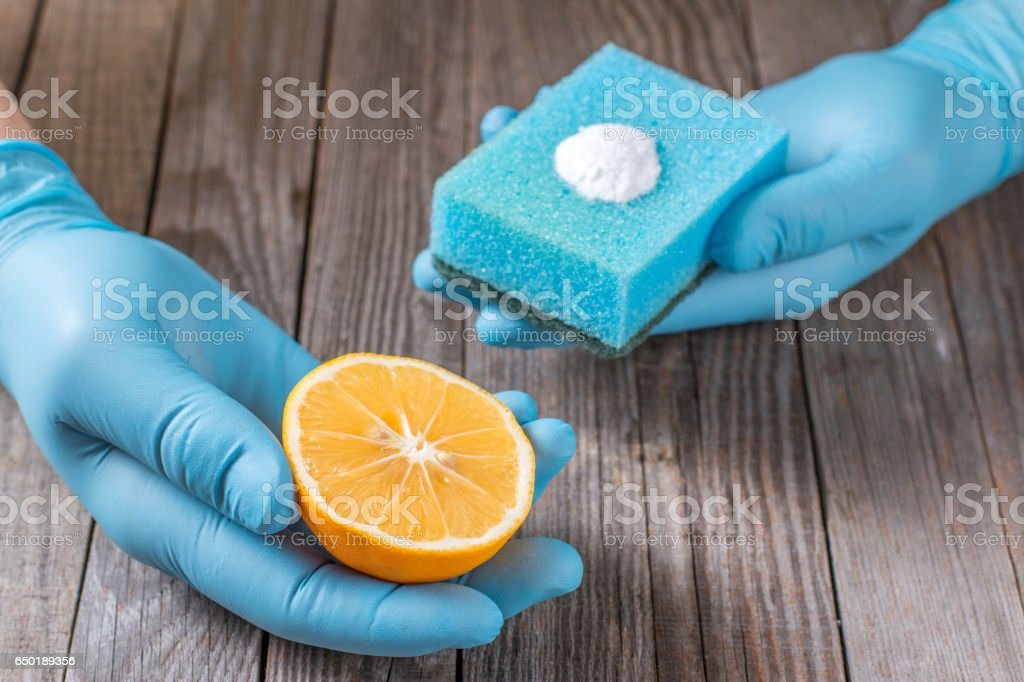 lemon and sodium bicarbonate in hand on wooden table stock photo