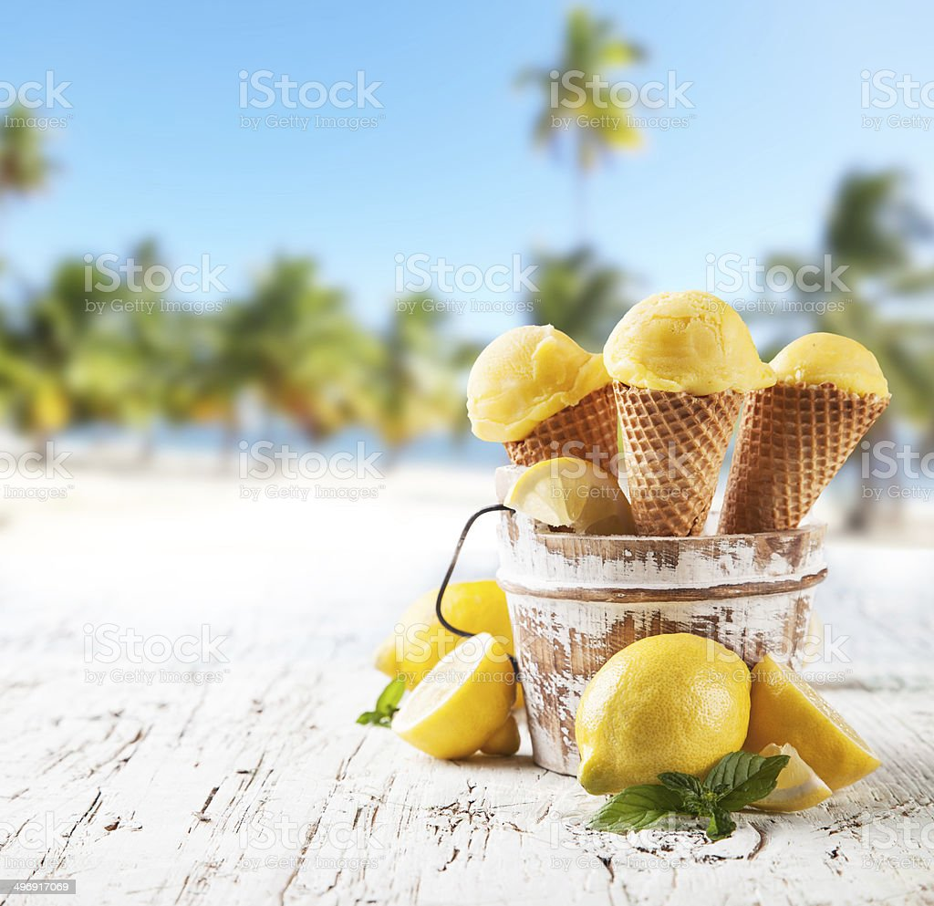 Lemon cce cream scoops in cones with blur beach stock photo
