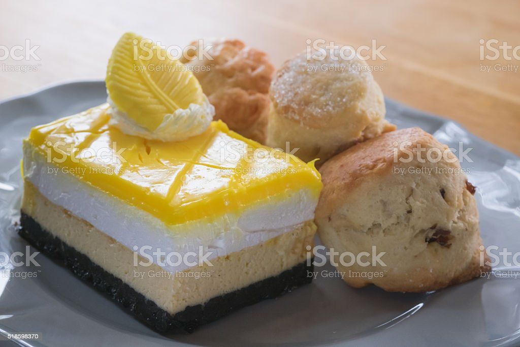 Lemon cheesecake with chocolate and scone at tea time stock photo