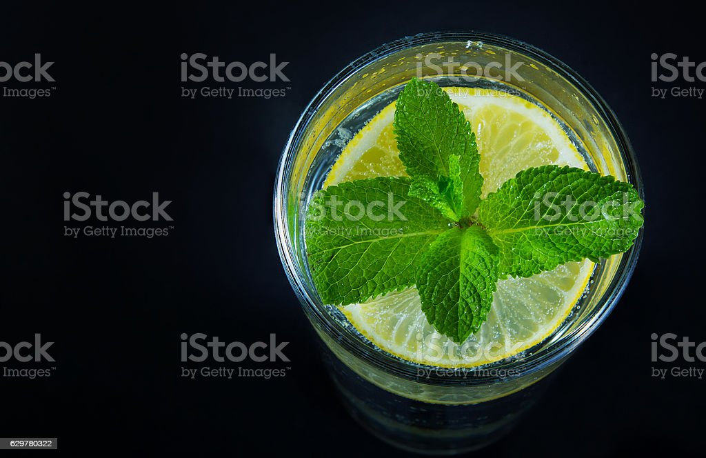 Lemon drink and mint on the black background royalty-free stock photo