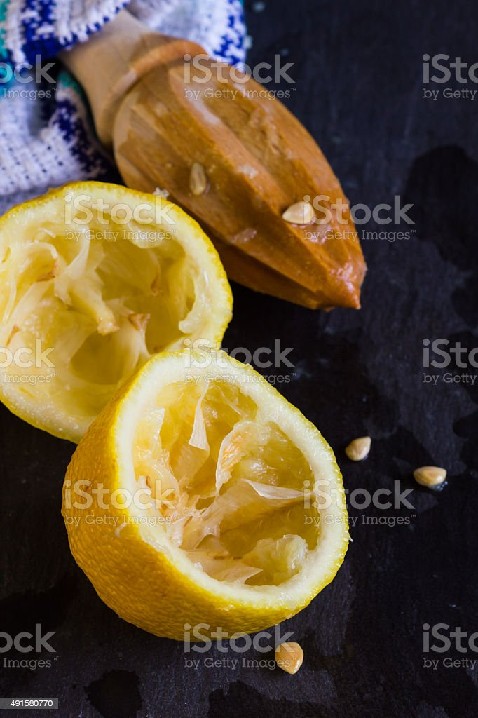 Lemon halves with fruit juicer on slate background with copyspace stock photo