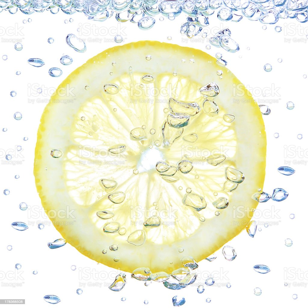 Lemon in a liquid with bubbles. royalty-free stock photo